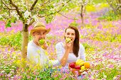 foto of love bite  - Young beautiful couple having picnic outdoors in summer time - JPG