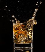 Isolated shot of whiskey splashing out of glass on black background