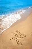 Happy New Year Written In Sand On Tropical Beach