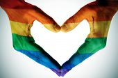 stock photo of gay symbol  - man hands painted as the rainbow flag forming a heart - JPG