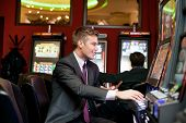 Happy man gambling on slot machine in casino