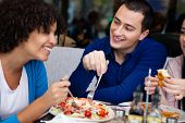 young affectionate couple having lunch in restaurant with friends