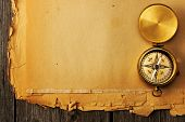 Antique brass compass over old paper background