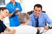 stock photo of hypertensive  - medical doctor checking senior patient - JPG