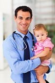 stock photo of pediatrics  - handsome pediatric doctor holding a baby girl - JPG