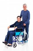 smiling middle aged man pushing handicapped wife on wheelchair isolated on white background