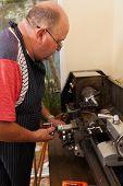 senior man using industrial lathe machine