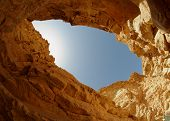Blue sky seen from the bottom of a desert canyon