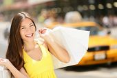 Happy shopper woman holding shopping bags, New York City, Manhattan, USA. Beautiful fresh joyful fem