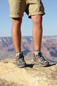 Hiking shoes on hiker in Grand Canyon. Man hikers hike boots in closeup with breathtaking view of Gr