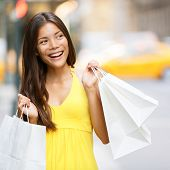 Shopping woman in New York City, Manhattan, USA. Shopper holding shopping bags walking smiling happy during shopping spree in outside. Young multiracial Asian Caucasian female model in yellow dress.