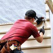 stock photo of red siding  - First time home buyer works to install siding on his new home - JPG