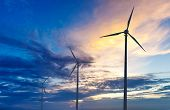 Green renewable energy concept - wind generator turbines sihouettes on sunset