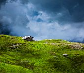 Serenity serene lonely scenery background concept - house in hills in mountins on alpine meadow in c