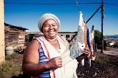 foto of curvaceous  - plump african woman proudly showing off her clean washing in the township - JPG