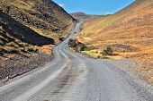 A gravel road winds among the hills and mountains.  Chilean Patagonia. Summer in the national park T