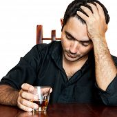 Portrait of an hispanic man holding an alcoholic drink suffering a headache (isolated on white)