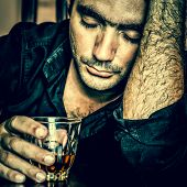 Alcoholism : Grunge blue toned portrait of a lonely and desperate drunk hispanic man