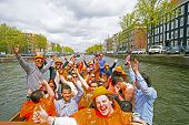 AMSTERDAM, NETHERLANDS - APRIL 30: People in orange cruising through the canals from Amsterdam durin