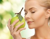 beautiful young woman smelling fresh green apple
