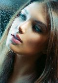 Portrait of Beauty Girl behind the Wet Glass. Melancholy Woman. Rain. Beautiful Model Looking Throug