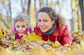 Mother and her little daughter lie in autumn park in drift of fallen leaves, low angle view