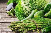 stock photo of abundance  - Fresh green organic  vegetables on wooden table