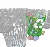 stock photo of waste reduction  - Many trash bins with only the recycling bin containing discarded papers - JPG