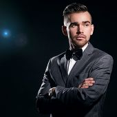 Portrait of a handsome man in a suit who is posing over a black background with a blue particles behind him