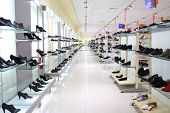 SAMARA, RUSSIA - JULY 7: A lot of women shoes on a glass shelf in a long hall of a shoe store with i