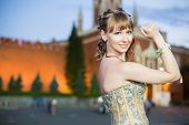 A young girl in a beautiful dress with a ribbon on hand standing next to the Kremlin