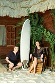 Man with surfboard hunkers and young woman sits on wooden chair next to beach house.