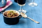 stock photo of red shallot  - boeuf bourguignon classic french beef stew on blue table with a glass of red wine - JPG