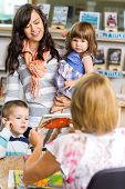 pic of librarian  - Mother and children looking at librarian showing book in library - JPG