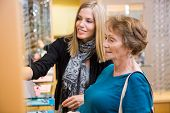 Salesgirl assisting senior female customer in selecting glasses at store