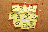 stock photo of tasks  - A wall calendar on a cork notice board covered with yellow sticky paper notes as a reminder of household chores and errands to be done - JPG