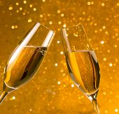 Two Champagne Flutes With Golden Bubbles On Golden Light Bokeh Background