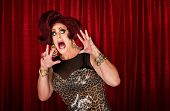 stock photo of drag-queen  - Scared drag queen with hands up in theater - JPG