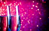 Champagne Flutes With Gold Bubbles On Blue And Violet Tint Light Bokeh Background