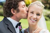 Groom kissing his pretty blonde wife on the cheek in the countryside
