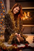 Happy christmas portrait of laughing woman in dressing gown decorating with tinsel and bulb, cosy li