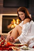 Happy attractive woman sitting by cosy fireplace, arranging christmas decoration, smiling.