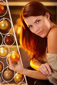 Cosy christmas portrait of smiling beauty by modern christmas tree with bulb handheld, bright light