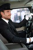 Elegant chauffeur driving luxurious car, smiling.