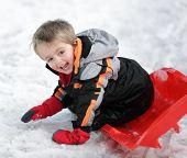 Happy young boy out playing in the snow on his sledge