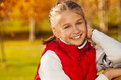 picture of 11 year old  - Close portrait of happy blond 11 years old girl with amazing smile sitting on the bench in the autumn park on sunny day - JPG