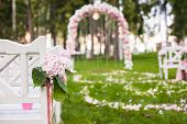 foto of wedding arch  - Wedding benches and flower arch for a wedding ceremony outdoors - JPG