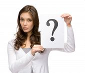 Half-length portrait of amazed woman holding question mark, isolated on white. Concept of problem and possible solution
