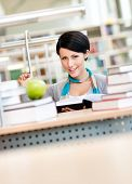Female student with green apple studies sitting at the desk at the reading hall of the library. Stud