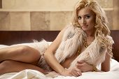 image of legs apart  - Beautiful and sexy sensuality young adult blonde woman wearing elegance fashionable fur and gold jewelry on the bed in luxury style apartment - JPG